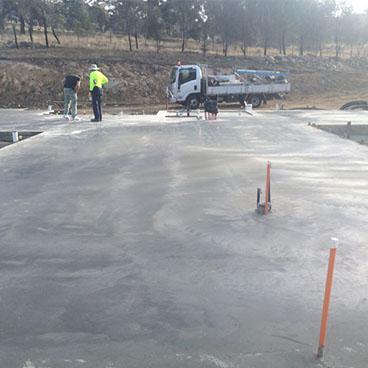 Multi Unit Concrete Slab With Concrete Truck And Contractors Inspecting  Site.